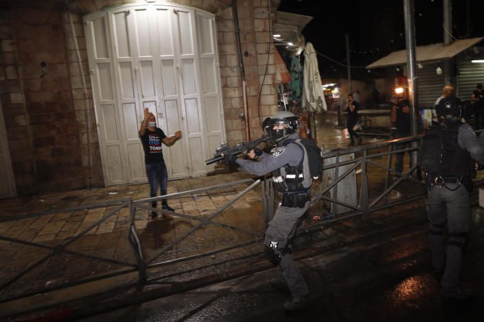 Israeli police officers aims his rifle during clashes with Palestinians near Damascus Gate just outside Jerusalem's Old City, Sunday, May 9, 2021. Israeli police have been clashing with Palestinian protesters almost nightly in the holy city's worst religious unrest in several years. (AP Photo/Ariel Schalit)