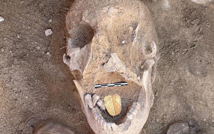 A decayed human skull with a clearly visible, golden-yellow amulet in its mouth - MINISTRY OF TOURISM AND ANTIQUTIES HANDOUT/EPA-EFE/Shutterstock