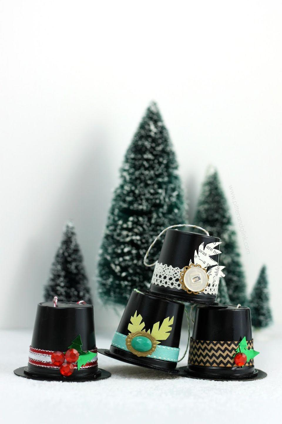 """<p>Turn K-cups into the cutest little to hats. </p><p><strong>Get the tutorial at <a href=""""http://www.pitterandglink.com/2014/12/recycled-k-cup-snowman-hat-ornaments.html"""" rel=""""nofollow noopener"""" target=""""_blank"""" data-ylk=""""slk:Pitter and Glink"""" class=""""link rapid-noclick-resp"""">Pitter and Glink</a>.</strong></p>"""