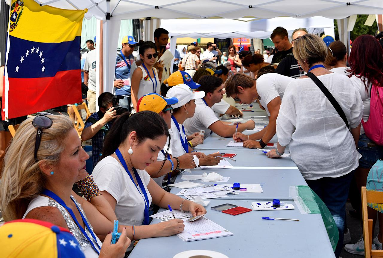<p>Venezuelan residents in Madrid register themselves at a polling station to vote during a symbolic plebiscite on president Maduro's project of a future constituent assembly, called by the Venezuelan opposition and held at the Plaza Colon in Madrid on July 16, 2017. (Gerard Julien/AFP/Getty Images) </p>
