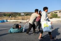 A man pulls a baby as refugees and migrants from the destroyed Moria move towards a new temporary camp during a police operation, on the island of Lesbos