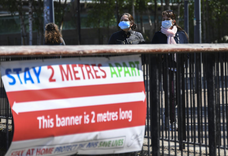 Two women wear protective masks as they walk past a social distancing banner on the south bank of the river Thames, as the lockdown due to the coronavirus outbreak continues, in London, Saturday, April 25, 2020.(AP Photo/Alberto Pezzali)