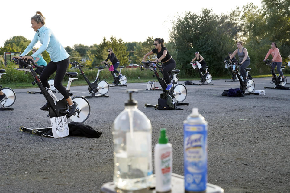 Jackie Brennan, of Merrimac, Mass., front left, pedals with others on stationary exercise bikes during a spinning class in a parking lot outside Fuel Training Studio, Monday, Sept. 21, 2020, in Newburyport. The gym's revenue is down about 60% during the COVID-19 pandemic. Fuel Training Studio plans to continue holding outdoor classes into the winter with the help of a planned greenhouse-like structure with heaters but no walls. (AP Photo/Steven Senne)