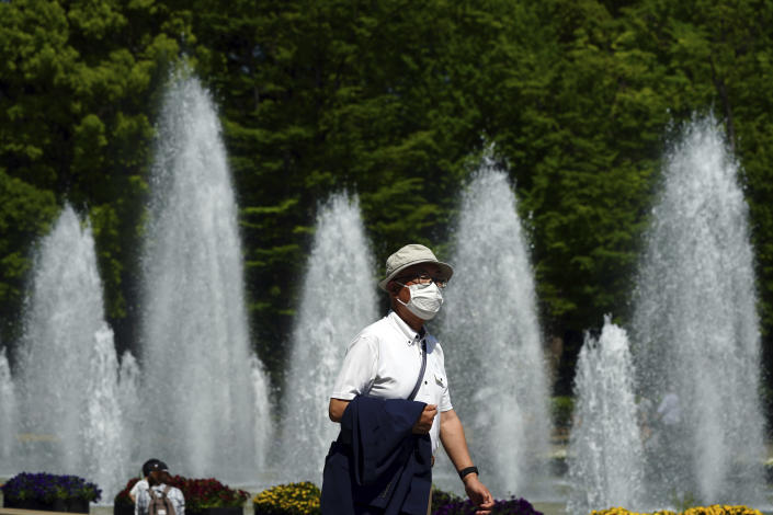 A man wearing a protective mask to help curb the spread of the coronavirus walks through a park Wednesday, April 21, 2021, in Tokyo. The Japanese capital confirmed more than 840 new coronavirus cases on Wednesday. (AP Photo/Eugene Hoshiko)