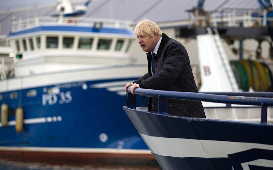 Prime Minister Boris Johnson looks on from aboard the Opportunis IV fishing trawler during a visit to Peterhead in Scotland - AFP