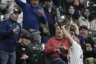 Fans watch as Milwaukee Brewers' Travis Shaw catches a foul ball hit by Pittsburgh Pirates' Gregory Polanco during the fourth inning of a baseball game Friday, April 16, 2021, in Milwaukee. (AP Photo/Morry Gash)