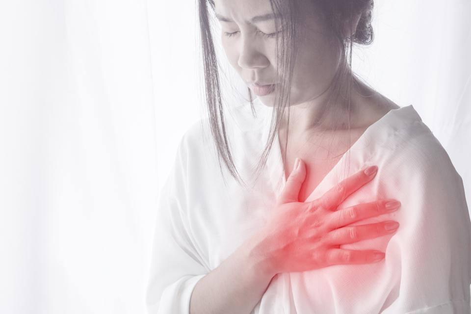 Asian woman standing against window with hand touching her chest in morning having heart attack