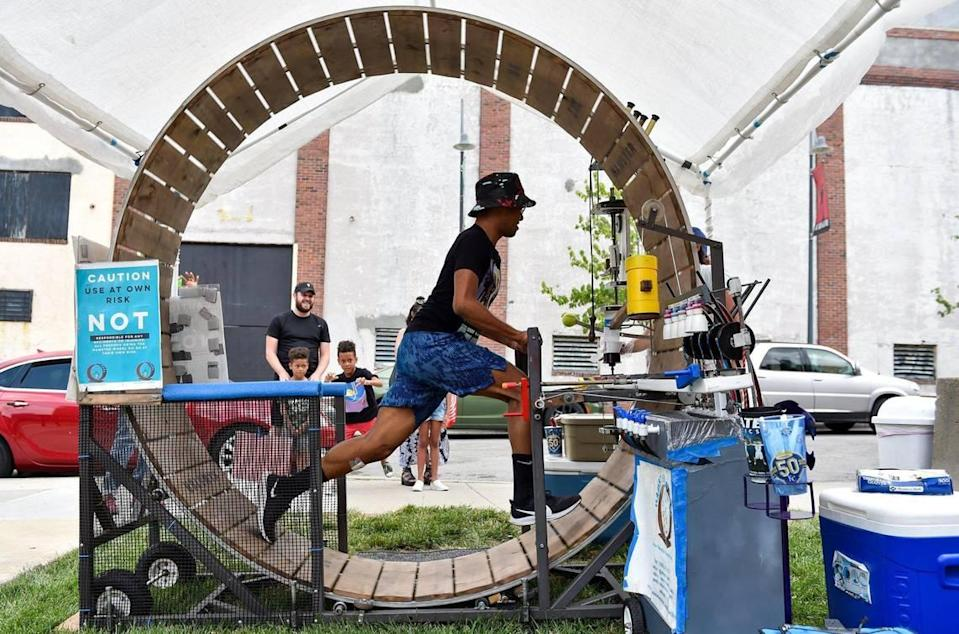 Raheem Fielder-Bey of Kansas City powers a hamster wheel to make his snow cone at Kansas City's Juneteenth Heritage Festival in the 18th and Vine Jazz District Saturday, June 19, 2021.