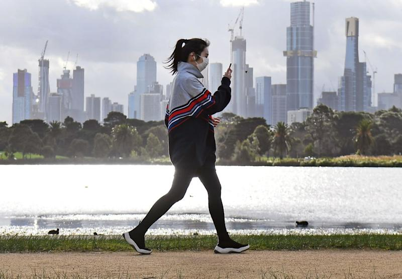 A woman exercises along Albert Park lake in Melbourne.