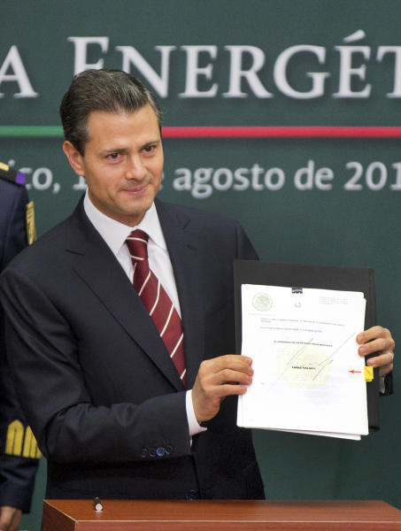Mexico's President Enrique Pena Nieto shows to the audience his proposal that would allow private firms to participate in the oil industry in Mexico City, Monday, Aug.12, 2013. Pena Nieto is making his most daring gamble yet, with a proposal to lift a decades-old ban on private companies in the state-run oil industry, a cornerstone of Mexico's national pride. (AP Photo/Eduardo Verdugo)