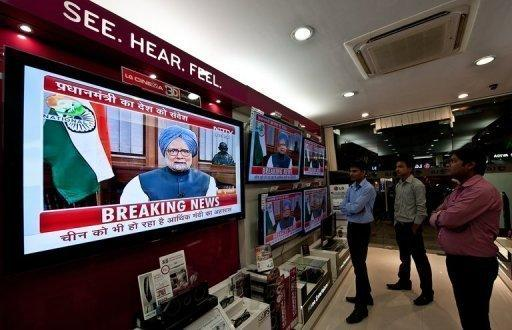 <p>People watch a televised speech by Indian Premier Manmohan Singh in New Delhi. While political opponents accused Singh of selling out the country to foreign interests, the media lauded him for addressing the difficulties facing Asia's third-largest economy.</p>