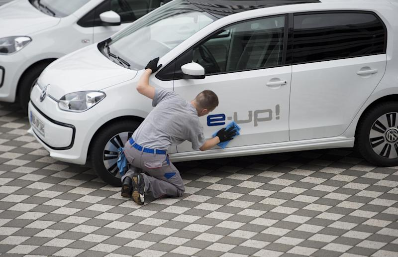 A worker polishes a VW e-up! electric car of German carmaker Volkswagen (VW) during a press event in Wolfsburg, on September 4, 2013 (AFP Photo/Johannes Eisele)
