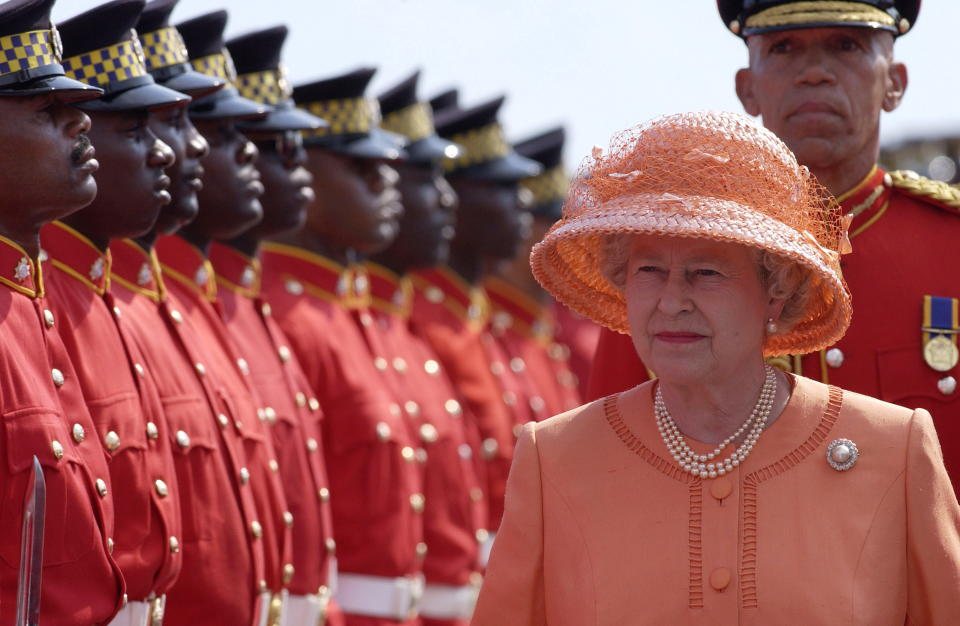 KINGSTON, JAMAICA - FEBRUARY 18:  Queen Elizabeth II Beginning Her Jubilee Tour In This Commonwealth Country Just Three Days After The Funeral Of Her Younger Sister.  Changing From Her Black Mourning Clothes She Chose A Bright Orange Colour To Celebrate This Important First Overseas Visit Of Her Jubilee Year.   She Is Inspecting A Guard Of Honour Of The Jamaica Defence Force.  (Photo by Tim Graham Photo Library via Getty Images)
