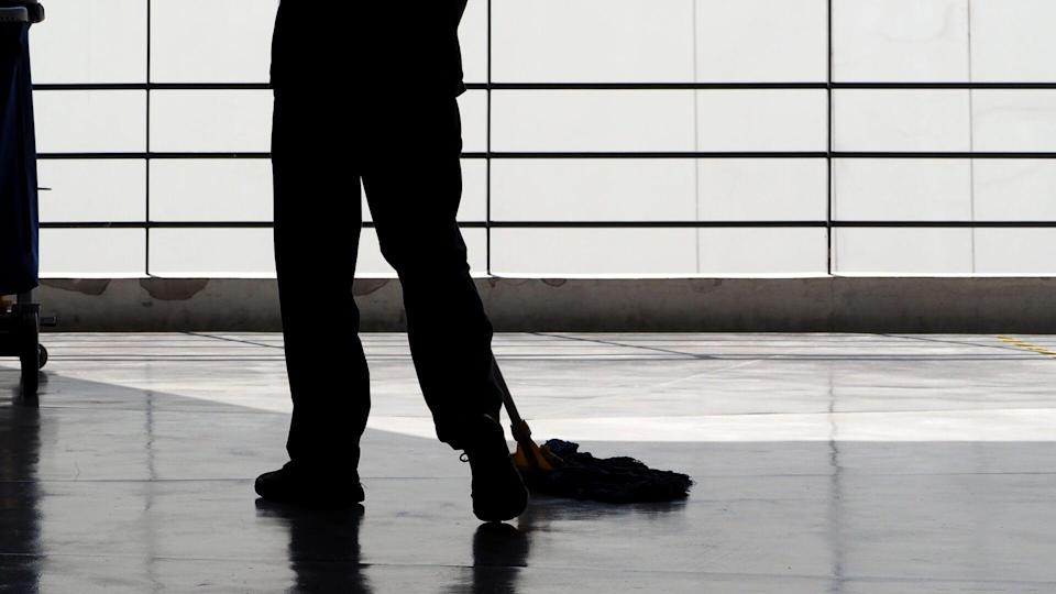 Silhouette image of cleaning service people sweeping floor with mop and other equipment on trolley.