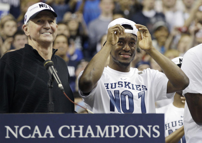 Connecticut guard Kemba Walker looks up at the school's honor board as his number 15 is listed with past athletic greats while standing with head coach Jim Calhoun during a pep rally the University of Connecticut in Storrs, Conn., Tuesday, April 5, 2011. Connecticut beat Butler for the national championship in the NCAA men's Final Four basketball tournament on Monday, April 4 in Houston. (AP Photo/Charles Krupa)