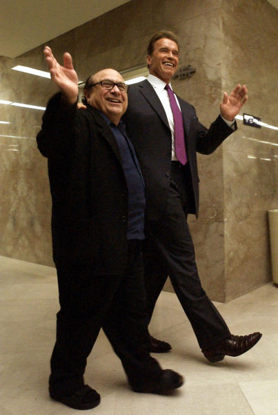 """FILE -- In this April 15, 2004 file photo, Actor Danny DeVito, left, waves as he walks through the Capitol with long-time friend, movie co-star and current Governor of California, Arnold Schwarzenegger, in Sacramento, Calif. Schwarzenegger, who came to office during California's historic 2003 recall election, will soon be releasing his autobiography, """"Total Recall: My Unbelievably True Life Story.""""(AP Photo/Rich Pedroncelli, file)"""