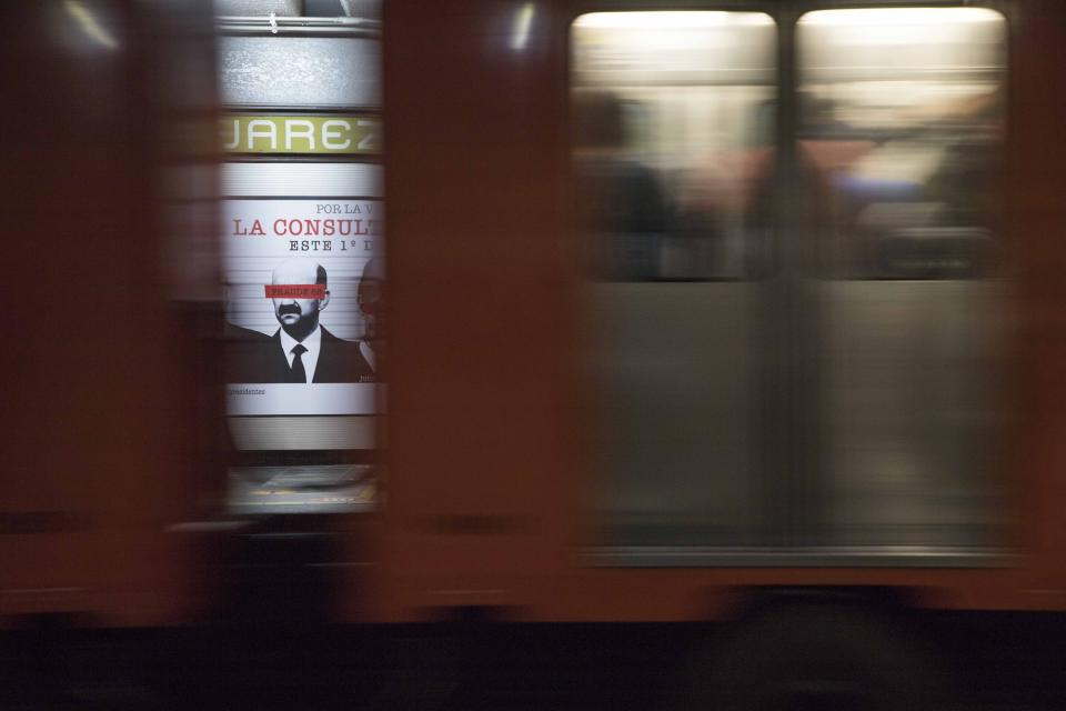 A subway going past frames an advertisement showing an image of Mexican former President Carlos Salinas, obscuring his eyes with a red bar, and calling for citizens to participate in a referendum on whether ex-presidents should be tried for their alleged crimes during their time in office, in Mexico City, Saturday, July 31, 2021. The yes-or-no referendum on Sunday is going to cost Mexico about $25 million, and the vote is being held in the middle of a third wave of the coronavirus pandemic. (AP Photo/Christian Palma)