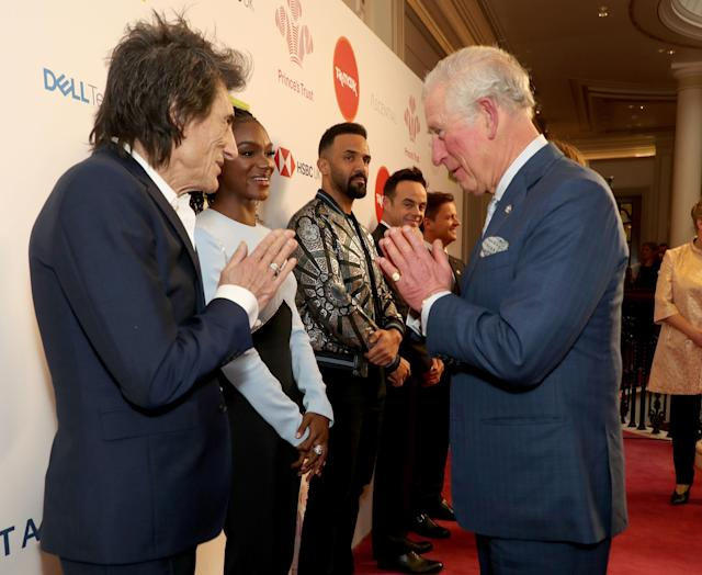 Charles greets Ronnie Wood with a namaste gesture. (Getty Images)