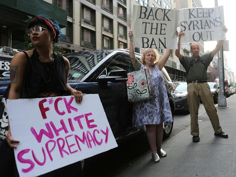 A protester against U.S. President Donald Trump's limited travel ban, approved by the U.S. Supreme Court, holds a sign next to protesters supporting the ban, in New York City, U.S., June 29, 2017: Reuters