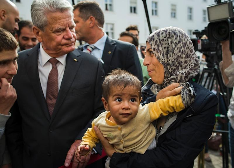 German President Joachim Gauck (L) speaks with Syrian refugees, 7-month-old baby Adam and his mother, Hanna (R), during a visit to a centre for asylum seekers in Berlin on August 26, 2015 (AFP Photo/Odd Andersen)