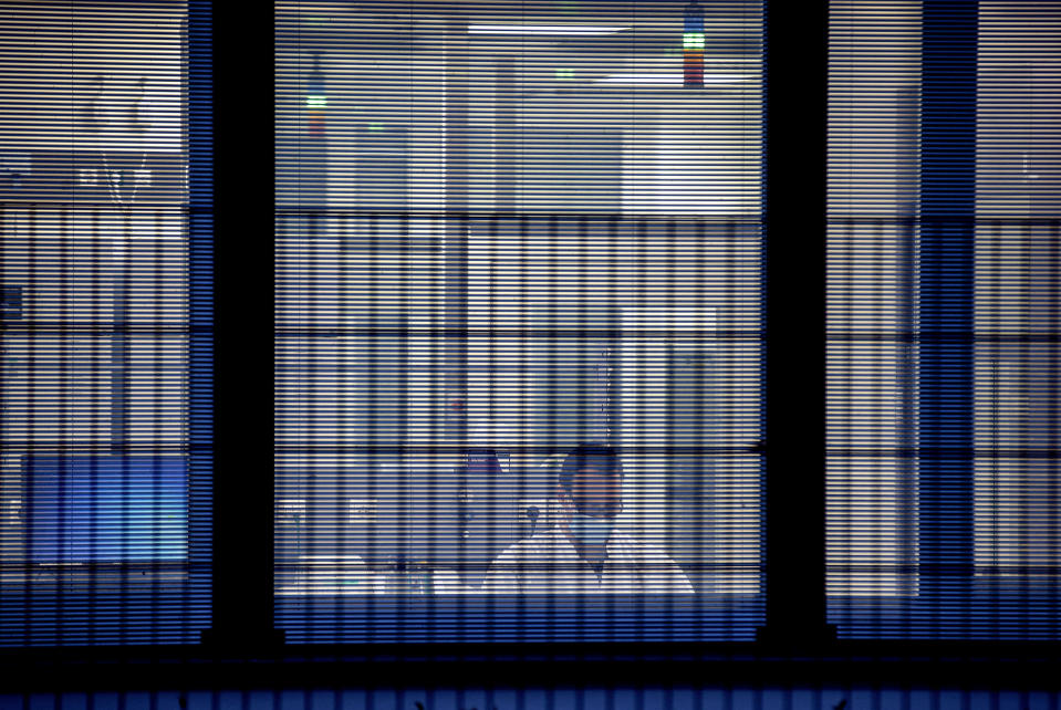 """File -- In this Tuesday, Nov.10, 2020 file photo a laboratorian works behind jalousies at the headquarters of the German biotechnology company """"BioNTech"""" in Mainz, Germany. Germany prepares for the vaccination of the German population during the upcoming month. (AP Photo/Michael Probst, file)"""