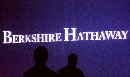 FILE PHOTO: Berkshire Hathaway shareholders walk by a video screen at the company's annual meeting in Omaha May 4, 2013. REUTERS/Rick Wilking/File Photo