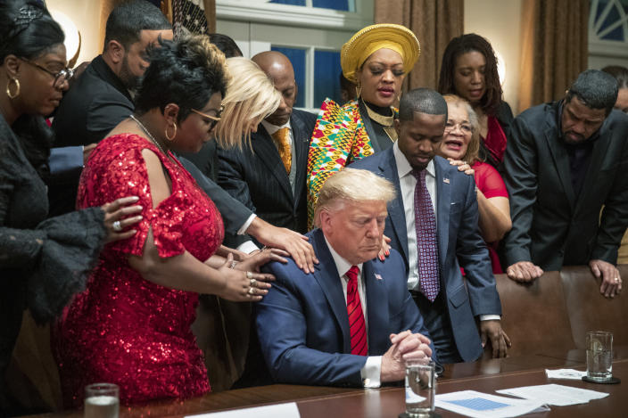FILE - In this Thursday, Feb. 27, 2020, file photo, African American leaders say a prayer with President Donald Trump as they end a meeting in the Cabinet Room of the White House, in Washington. Trump's appeal to religious conservatives is a cornerstone of his political identity. But Joe Biden is a different kind of foe than Trump has faced before: one who makes faith a central part of his persona – often literally wearing it on his sleeve. (AP Photo/Manuel Balce Ceneta, File)