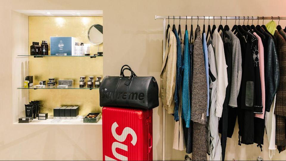 A rack of used men's clothes, and one leather Supreme duffel bag, at The RealReal