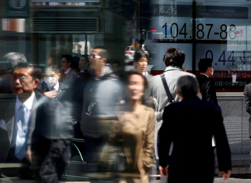 FILE PHOTO: People walk past an electronic board showing exchange rate between Japanese Yen and U.S. Dollar outside a brokerage at a business district in Tokyo, Japan, March 23, 2018. REUTERS/Toru Hanai/File Photo