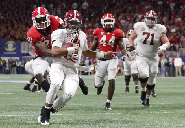 Georgia defensive back J.R. Reed (20) tries to tackle Alabama quarterback Jalen Hurts (2) during the second half of the SEC title game on Saturday. (AP)
