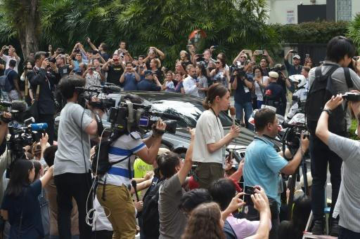 Journalists and onlookers watch the motorcade carrying North Korean leader Kim Jong Un arriving at the St. Regis hotel
