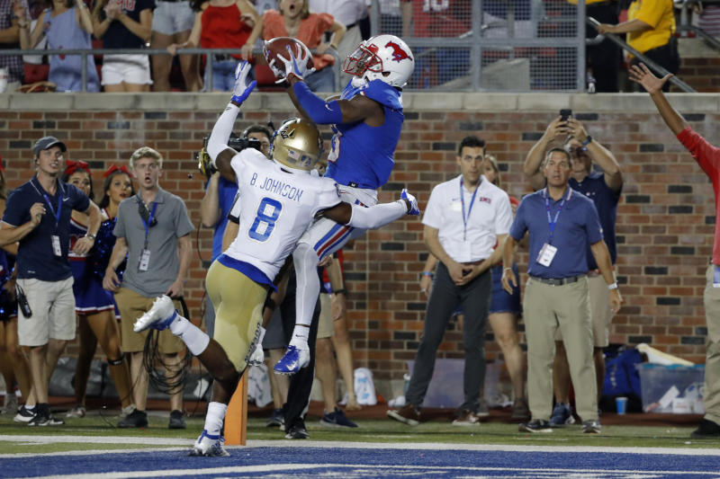 SMU wide receiver James Proche, in blue, catches a touchdown pass while Tulsa safety Brandon Johnson (8) defends during the third overtime of an NCAA college football game Saturday, Oct. 5, 2019, in Dallas. SMU beat Tulsa 43-37. (AP Photo/Roger Steinman)