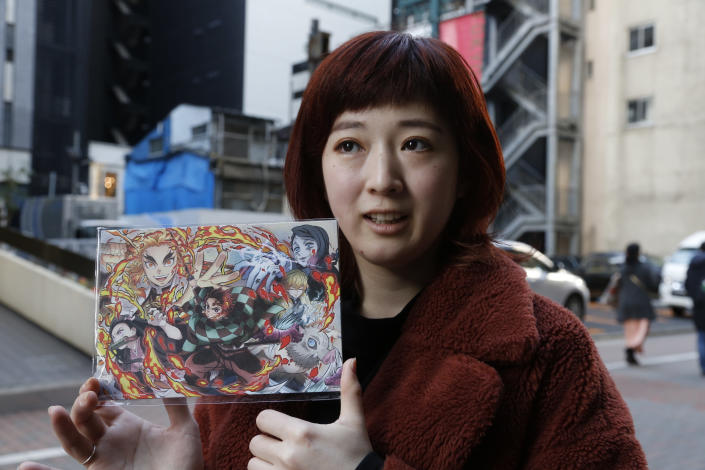 "Japanese hairstylist Akina Nasu shows a picture she got when she went to see the film ""Demon Slayer,"" which has become the nation's top-grossing film, and opened in Miami to be eligible for the 2021 Academy Awards, in Tokyo Wednesday, March 3, 2021. Nasu and other fans says they identify with the story because of the hardships and fears during the coronavirus pandemic. (AP Photo/Yuri Kageyama)"