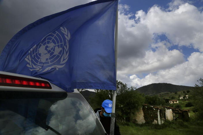 A U.N vehicle with a U.N flag is seen inside the U.N controlled buffer zone that divide the Greek, south, and the Turkish, north, Cypriot areas since the 1974 Turkish invasion, Cyprus, on Friday, March 26, 2021. Cyprus' endangered Mouflon sheep is one of many rare plant and animal species that have flourished a inside U.N. buffer zone that cuts across the ethnically cleaved Mediterranean island nation. Devoid of humans since a 1974 war that spawned the country's division, this no-man's land has become an unofficial wildlife reserve. (AP Photo/Petros Karadjias)