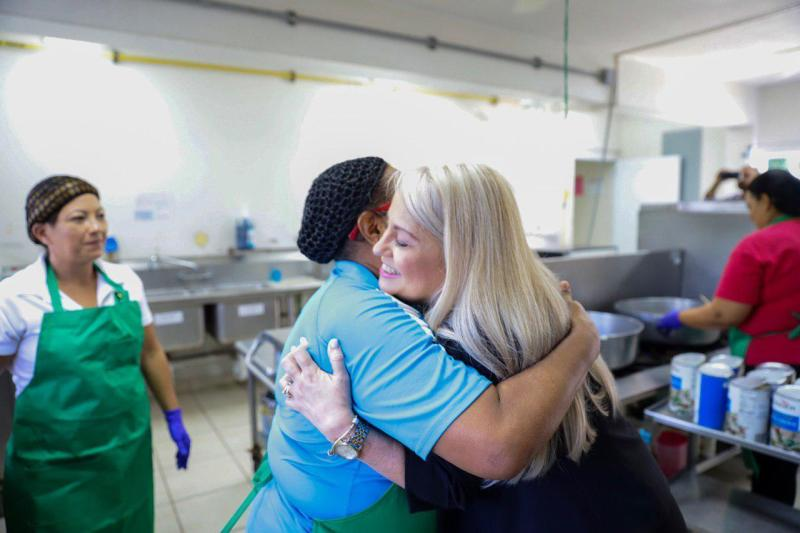In this handout photo provided by the Governor's Office, Puerto Rico Gov. Wanda Vazquez embraces a cafeteria worker during a visit to the Ramon Marin Sola School, in Guaynabo, Puerto Rico, Monday, Aug. 12, 2019. Vazquez visited the elementary school she attended as a child, marking the beginning of the 2019-2020 school year. (Governor's Office via AP)
