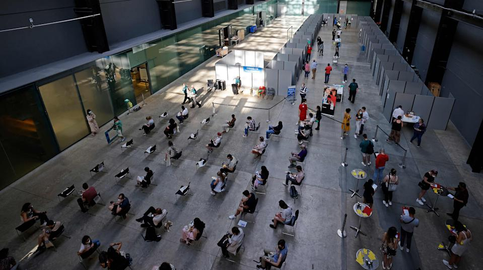 Members of the public wait to receive the Pfizer vaccine in the Turbine Hall at Tate Modern (AFP via Getty Images)