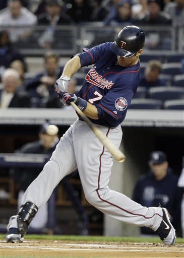 Minnesota Twins' Joe Mauer (7) follows througn on an RBI-double during the first inning against the New York Yankees at Yankee Stadium in New York, Wednesday, April 18, 2012. (AP Photo/Frank Franklin II)