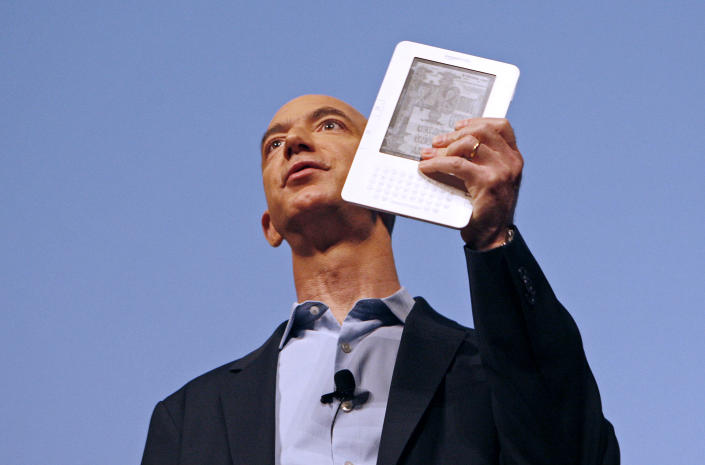 Amazon.com founder and CEO Jeff Bezos holds the new Kindle 2 electronic reader at a news conference in New York where the device was introduced, February 9, 2009. The Kindle 2, the latest incarnation of the digital book reader is a slimmer version with more storage and a feature that reads text aloud to users.  REUTERS/Mike Segar  (UNITED STATES)