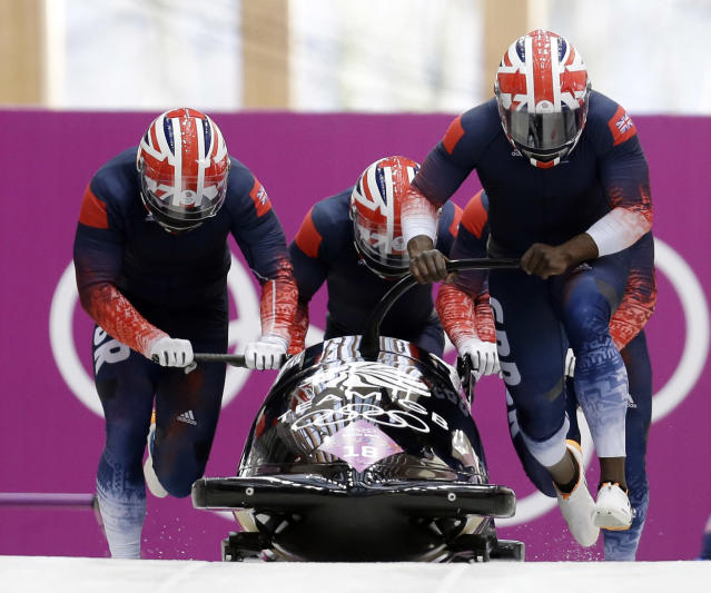 The team from Great Britain GBR-2, with Lamin Deen, John Baines, Andrew Matthews and Ben Simons, start their first run during the men's four-man bobsled competition final at the 2014 Winter Olympics, Sunday, Feb. 23, 2014, in Krasnaya Polyana, Russia. (AP Photo/Natacha Pisarenko)