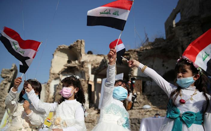 Girls wave national flags as they gather at Church square ahead of Pope Francis' arrival to visit Mosul, Iraq, March 7, 2021. - REUTERS/Yara Nardi
