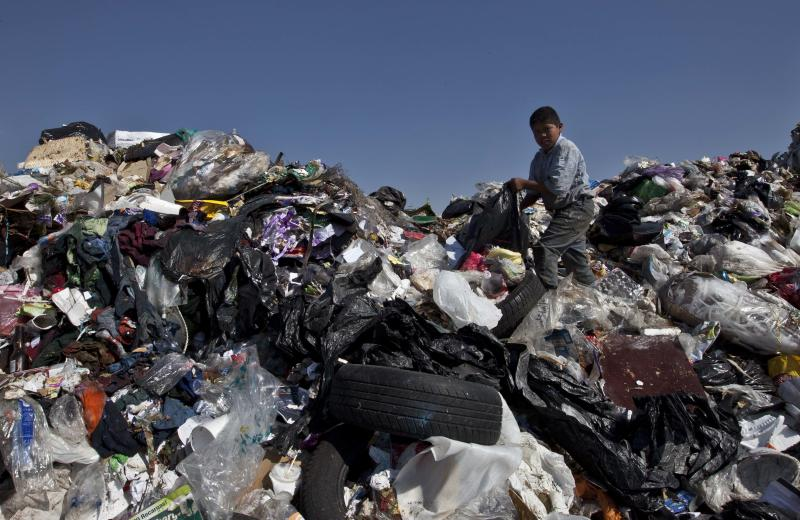 FILE - In this Dec. 19, 2011 file photo, a boy selects garbage to recycle at the landfill Bordo Poniente on the outskirts of Mexico City. This dump was closed at the end of 2011 but the compost site within the dump continues to operate. Mexico City Mayor Miguel Mancera announced plans in September 2013 to control the foul odors that waft from the city's only compost plant at this landfill near the airport and to more aggressively recycle trash citywide. (AP Photo/Christian Palma, File)