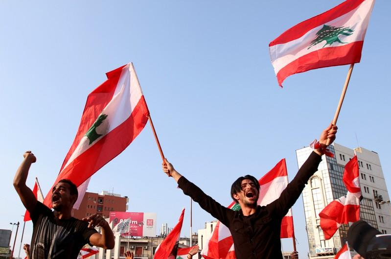 Demonstrators carry national flags and gesture during an anti-government protest in Tripoli