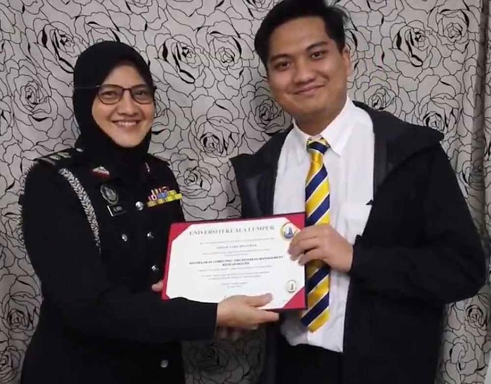 Ahmad Nabil (right) receiving his graduation certificate from his mother in his creative home convocation ceremony. — Twitter/AhmadNabil