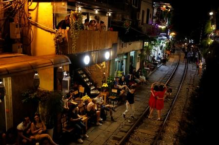 Tourists sit in cafes near a railway track as others take a picture on it, along a street in the Old Quarter of Hanoi, Vietnam