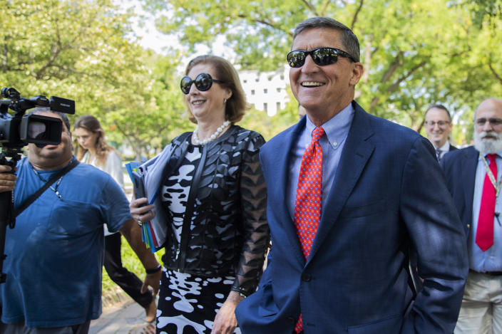 FILE - In this Sept. 10, 2019, file photo, Michael Flynn, President Donald Trump's former national security adviser from Middletown, R.I., leaves federal court with his lawyer Sidney Powell, left, following a status conference in Washington. On Nov. 25, 2020, Trump pardoned Flynn despite Flynn's guilty plea to lying to the FBI about his Russia contacts. (AP Photo/Manuel Balce Ceneta, File)