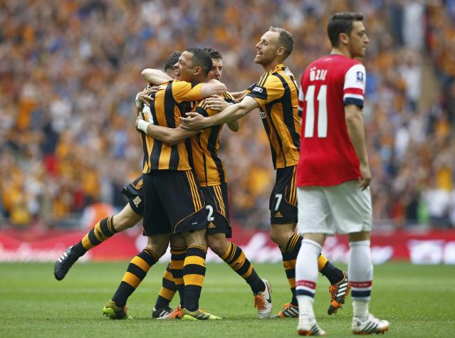 Hull City players celebrate with their team mate James Chester (L) after he scored his team's first goal, as Arsenal's Mesut Ozil (R) reacts, during their FA Cup final soccer match at Wembley Stadium in London, May 17, 2014. REUTERS/Darren Staples (BRITAIN - Tags: SPORT SOCCER)