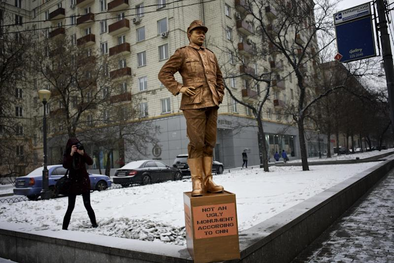 """FILE - In this photo taken on Friday Feb. 7, 2014 a member of pro-Kremlin Young Guards of United Russia photographs a monument to a Nazi soldier outside a building, where the CNN Moscow office is located, as a protest against the CNN poll on the most ugly monuments in the world, which included the WWII monument in Brest, Belarus. U.S. television network CNN caused a firestorm when it included a war monument in Brest, a city in the former Soviet republic of Belarus, in an article on the """"world's ugliest monuments"""" published Jan. 24. (AP Photo/Alexander Zemlianichenko, file)"""