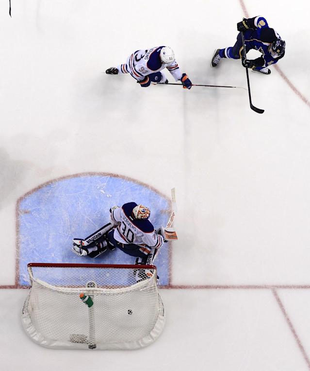 St. Louis Blues' Vladimir Tarasenko, of Russia, scores past Edmonton Oilers goalie Ben Scrivens (30) and Ryan Nugent-Hopkins (93) during the second period of an NHL hockey game, Thursday, March 13, 2014, in St. Louis. (AP Photo/Jeff Roberson)
