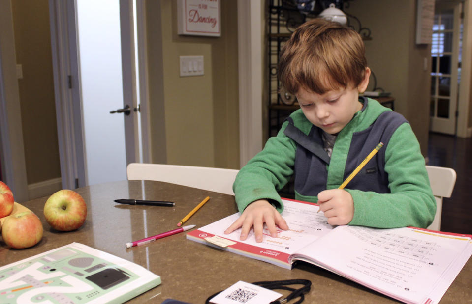 Charlie Dale works on problems in his math notebook at the kitchen counter in his family home in Lake Oswego, Ore., Oct. 30, 2020. Charlie's school has been closed to in-person learning since March. In Oregon, one of only a handful of states that has required a partial or statewide closure of schools in the midst of the COVID-19 pandemic, parents in favor of their children returning to in-person learning have voiced their concerns and grievances using social media, petitions, letters to state officials, emotional testimonies at virtual school board meetings and on the steps of the state's Capitol. (AP Photo/Sara Cline)
