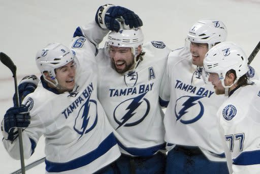 Tampa Bay Lightning Nate Thompson, second from left, celebrates his overtime goal against the Montreal Canadiens in an NHL game in Montreal, Saturday, Feb. 1, 2014. The Lightning won 2-1 in overtime. (AP Photo/The Canadian Press, Peter McCabe)